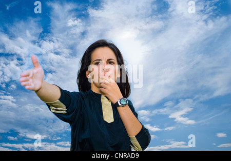 Woman blowing whistle against blue sky - Stock Photo