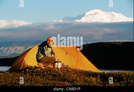 woman camping in front of the highest mountain of Nort America, Mt. McKinley, USA, Alaska, Denali Nationalpark - Stock Photo