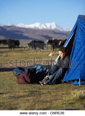 Woman putting on shoes in camping tent - Stock Photo