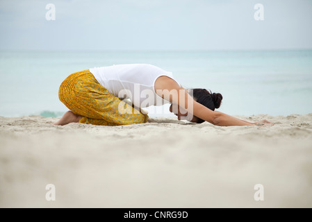 Woman in childs pose on beach, side view - Stock Photo