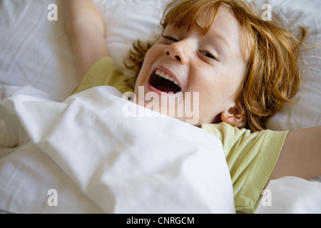 Boy lying in bed - Stock Photo