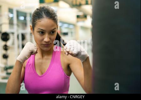 Young woman punching heavy bag - Stock Photo