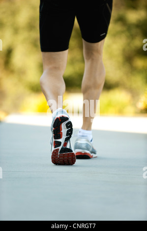 Man in sport shoes walking, low section, rear view - Stock Photo