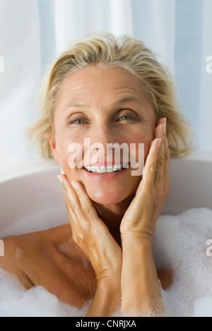 Mature woman enjoying bubble bath, portrait - Stock Photo