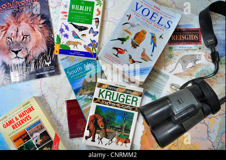 Binoculars, travel guides, guidebooks, African wildlife determination books and South African map for planning safari - Stock Photo