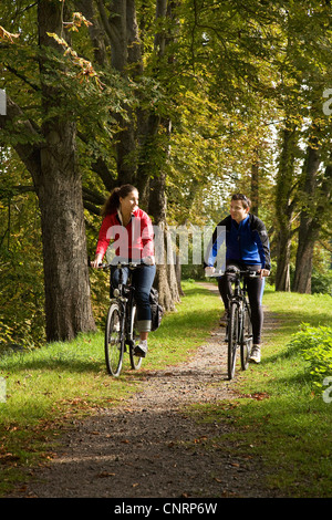 young couple on bicycles at ruhr valley cycleway at avenue near Kemnade Castle, Germany, North Rhine-Westphalia, - Stock Photo