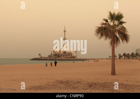 A beach in Kuwait City with the Marina Waves building in the background - Stock Photo