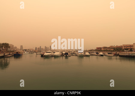Hazy view across the marina after a recent sand storm from Marina Mall and Marina Crescent in Kuwait City - Stock Photo