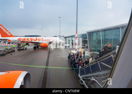 Amsterdam Schiphol Airport People boarding EasyJet plane airplane aeroplane mobile staircase stairs in winter. H - Stock Photo