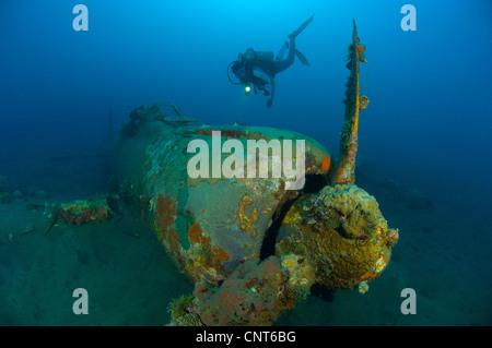 Diver explores the wreck of a Mitsubishi Zero fighter plane, Kimbe Bay, Papua New Guinea. - Stock Photo