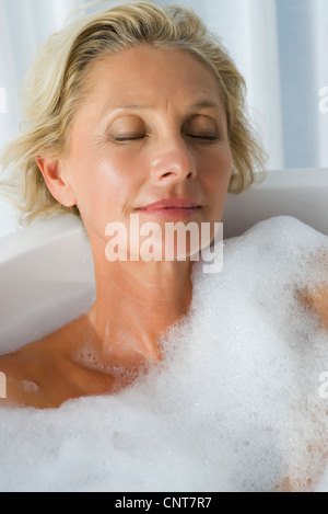 Mature woman relaxing in bubble bath with eyes closed, portrait - Stock Photo