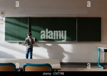 Boy standing in classroom, in front of blackboard, rear view - Stock Photo