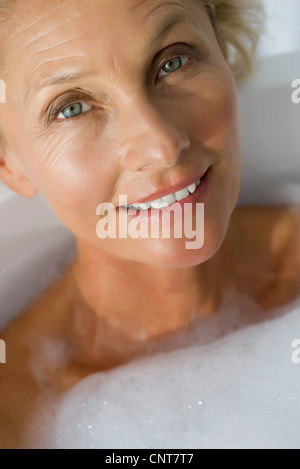 Mature woman relaxing in bubble bath, cropped - Stock Photo