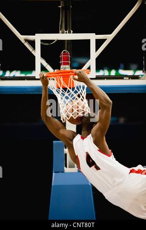 Basketball slam dunking, rear view - Stock Photo