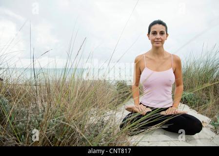 Mature woman sitting in lotus position on beach, portrait - Stock Photo