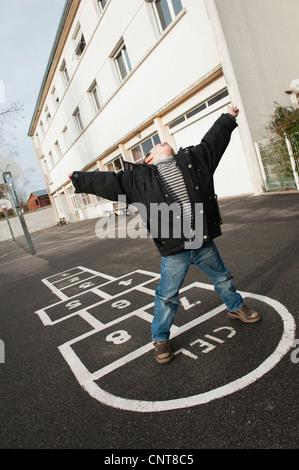 Boy playing hopscotch, tilt - Stock Photo