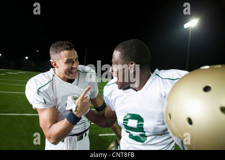 Football players celebrating victory together - Stock Photo
