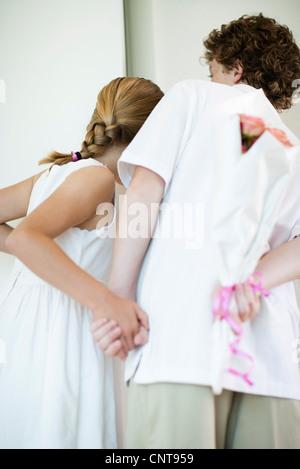 Young siblings holding bouqet of flowers behind backs, peeking through doorway - Stock Photo
