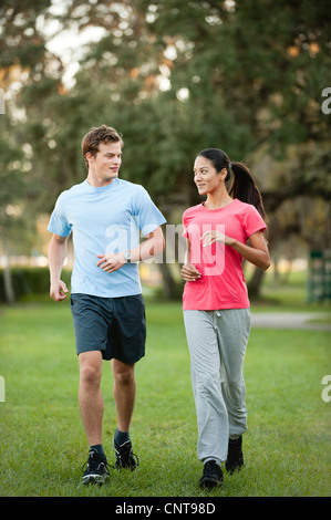 Young couple jogging on grass - Stock Photo