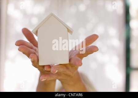Woman's hands holding small model house, cropped - Stock Photo