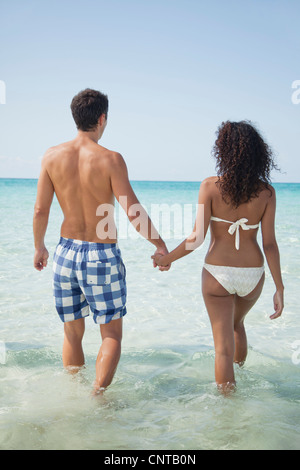 Couple holding hands while wading in sea, rear view - Stock Photo