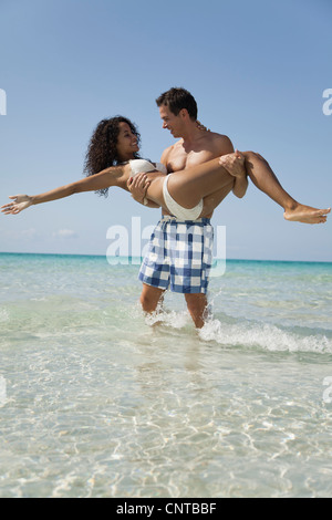 Couple together at the beach, man carrying woman - Stock Photo