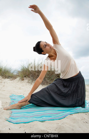 Mature woman doing yoga stretch on beach, portrait - Stock Photo