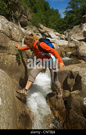 young woman crossing the Canyon of Chavezac, France, Lozere, Cevennes National Park - Stock Photo