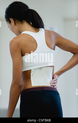 Woman with bandage on lower back, rear view - Stock Photo