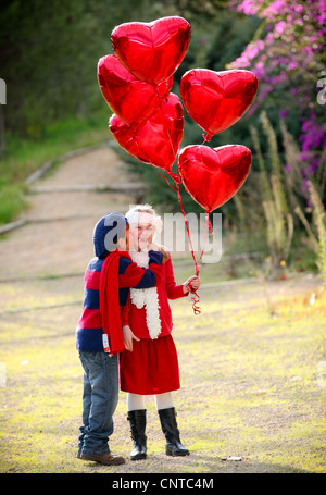 valentines kids with gift of balloons and kiss - Stock Photo