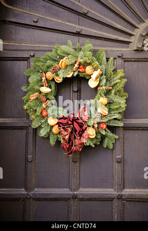 winter christmas holly wreath on old wooden door - Stock Photo