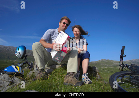 young couple taking a break during a cycle ride through the highlands, United Kingdom, Scotland, Sutherland, Loch - Stock Photo