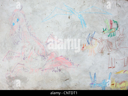 Child's drawing of a dragon on a cement wall - Stock Photo