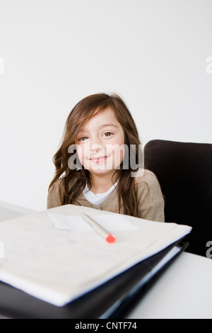 Girl doing her homework at desk - Stock Photo