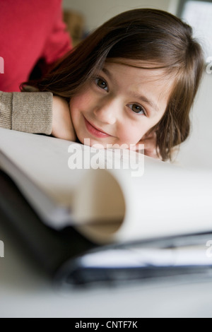 Smiling girl doing her homework at desk - Stock Photo
