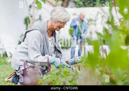 Older couple gardening in backyard - Stock Photo