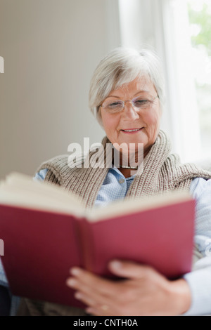 Smiling older woman reading book - Stock Photo