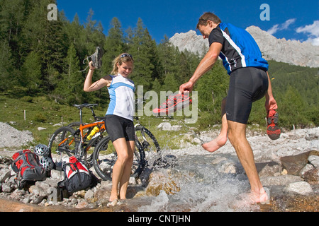 man and woman with mountain bikes on a tour in the alpine mountains, having fun at a mountain creek, Austria, Upper - Stock Photo