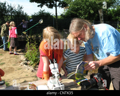 primary school pupils and teacher have caught animals in the self-built pond in the school garden and identify them - Stock Photo