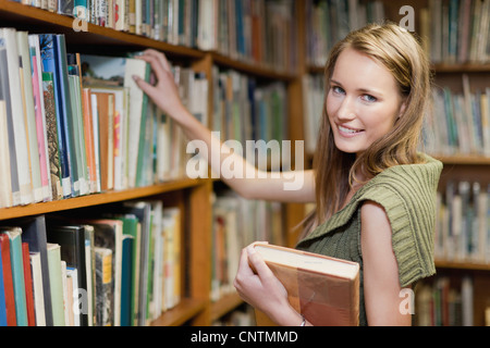 Student selecting books in library - Stock Photo