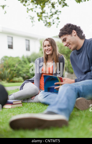 Students studying on grass on campus - Stock Photo