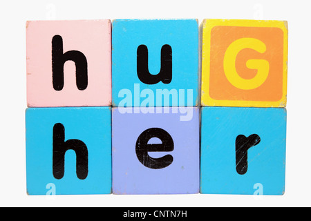 assorted childrens toy letter building blocks against a white background that spell hug her with clipping path - Stock Photo