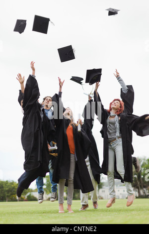 Graduates throwing caps in the air - Stock Photo