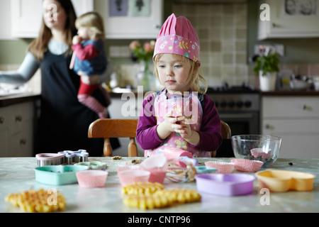 Toddler girl baking in kitchen - Stock Photo