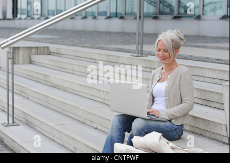 Older woman using laptop on steps - Stock Photo