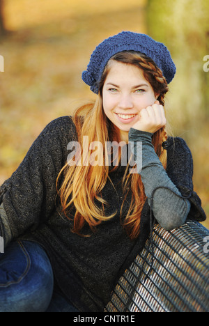 Teenage girl sitting on park bench - Stock Photo