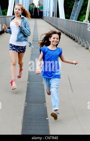 Girls running on bridge together - Stock Photo
