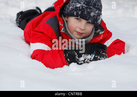 Boy in parka playing in snow - Stock Photo