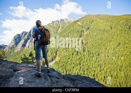 A woman hiker standing on the edge of a rocky cliff looking up at a mountain, Little Si Trail, Washington, USA. - Stock Photo