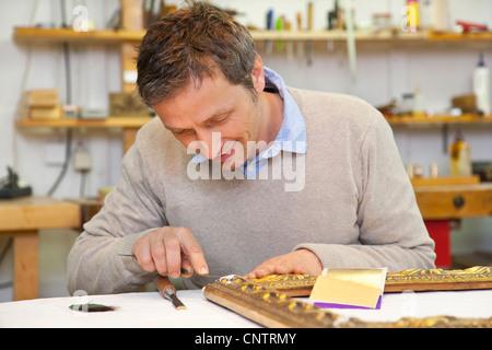 Carpenter working in shop - Stock Photo